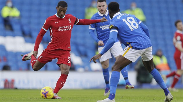 Giorginio Wijnaldum (Liverpool) nakopává míč před Dannym Welbeckem z Brightonu.