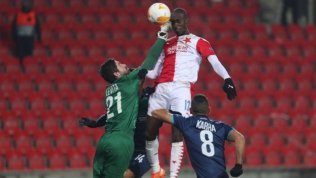 Slávista Abdallah Sima se pokouší hlavičkovat, proti němu boxující brankář Beer Ševy Ohad Levita.