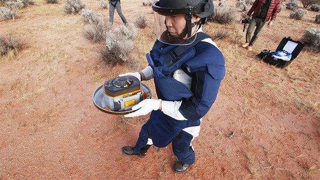 Jeden z astronomů z japonské kosmické agentury JAXA nese kapsli se vzorky dopravenımi sondou Hajabusa 2.
