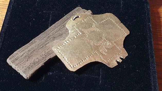 Zlatı plech s nápisem IR, nejspíše z víka relikviáře.