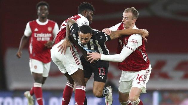 Callum Wilson  z Newcastlu bojuje s dvojicí Thomas Partey (vlevo) a Rob Holding z Arsenalu.