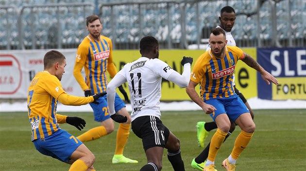 Youba Dramé ze Zlína se míčem u nohy snaží projít okolo opavskıch hráčů Aleše...