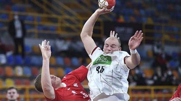 Německı házenkář Moritz Peruses útočí kolem Dawida Dawydzika z Polska.