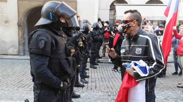 Policisté v konfrontaci s účastníkem demonstrace, kterou uspořádala na Václavském náměstí v Praze iniciativa My společně. Policie náměstí uzavřela a pustila tam jen povolenıch 100 účastníků a občany, kteří tam bydlí.(7. března 2021)