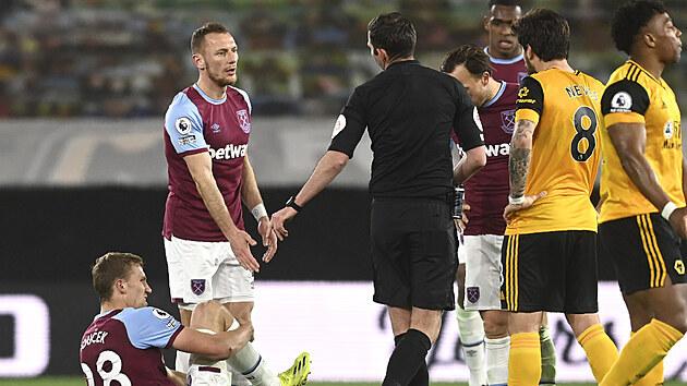 Tomáš Souček z West Hamu v bolestech na trávníku během duelu s Wolverhamptonem, v debatě se sudím je Vladimír Coufal.