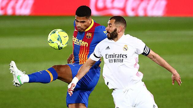 Ronald Araújo (vlevo) z Barcelony bojuje o balon s kapitánem Realu Madrid Karimem Benzemou.
