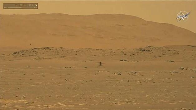 Snímek z kamery roveru Perseverance zachycující let vrtulníčku Ingenuity  na Marsu.