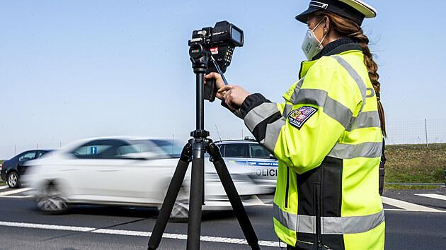 Policistka měří 21. dubna 2021 rychlost vozidel na sjezdu z dálnice D7 u Postoloprt na Lounsku.Místo vybrala policie na základě hlasování občanů. Do celoevropské bezpečnostní akce nazvané Speed Marathon se policejní hlídky zapojily pošesté.