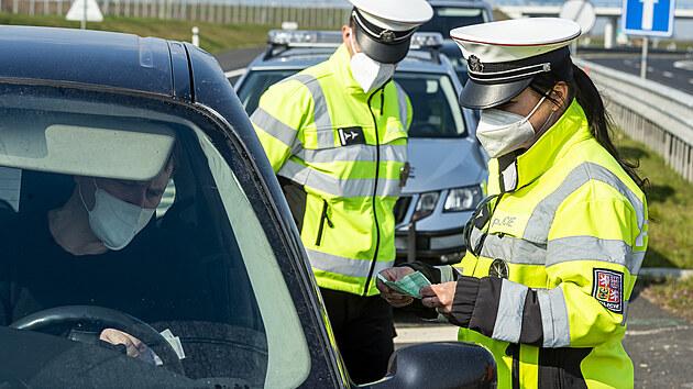 Policistka kontroluje 21. dubna 2021 doklady řidiči vozidla na sjezdu z dálnice D7 u Postoloprt na Lounsku, kde policisté měřili rychlost. Místo vybrala policie na základě hlasování občanů. Do celoevropské bezpečnostní akce nazvané Speed Marathon se policejní hlídky zapojily pošesté.