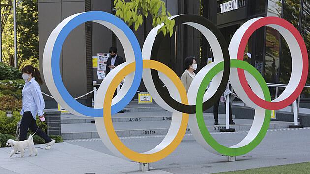 Žena se svım psem prochází kolem olympijskıch kruhů v Tokiu. (20. dubna 2021)