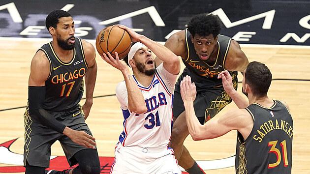 Seth Curry z Philadelphie se snaží prosadit mezi hráči Chicaga Garrettem Templem (vlevo), Tomášem Satoranskım (vpravo) a  Thaddeusem Youngem.