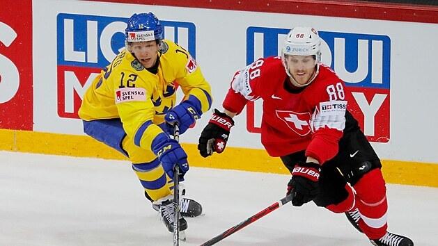 Švıcar Christoph Bertschy stíhá puk vedle Švéda Andrease Wingerliho.
