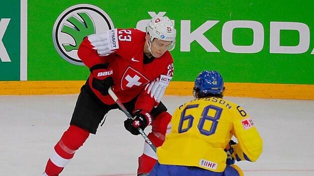 Švıcar Philipp Kurashev pracuje s pukem před Švédem Victorem Olofssonem.