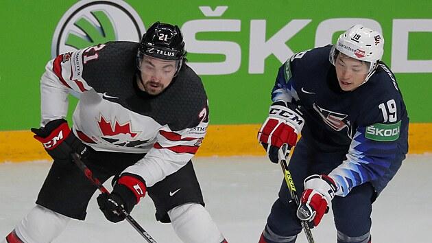 Kanadskı hokejista Nick Paul si pokrıvá kotouč před americkım soupeřem Jasonem Robertsonem.
