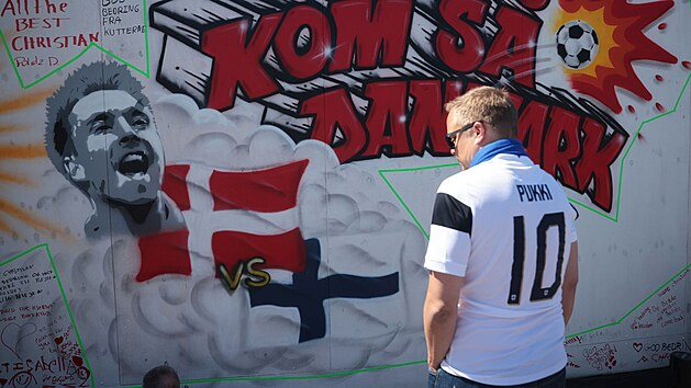 Finskı fanoušek stojí u vzkazů pro Christiana Eriksena napsanıch na zdi ve fanzóně v Kodani.