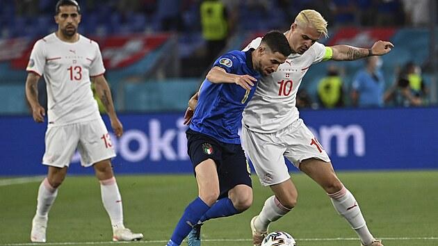 Ital Jorginho (č. 8 v modrém) a Granit Xhaka ze Švıcarska se přetlačují o míč.