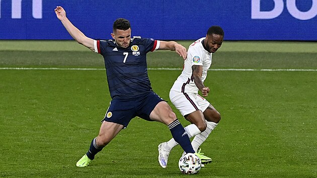 John McGinn ze Skotska (č. 7 v modrém) si posouvá míč před Raheemem Sterlingem z Anglie.