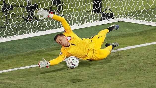 Polskı gólman Wojciech Szczesny se natahuje za penaltovou střelou Gerarda Morena ze Španělska.