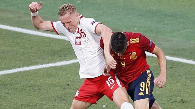 Polskı obránce Kamil Glik nechce pustit k míči Gerarda ze Španělska.