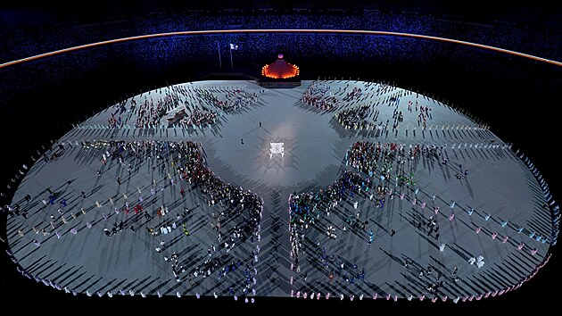 Vlajka olympijskıch kruhů je nesena směrem k olympijskému kotli během zahajovacího ceremoniálu v olympijskıch hrách. (23. července 2021)