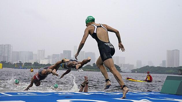 Číňanka Mengying Zhongová skáče do vody po startu triatlonového závodu žen.