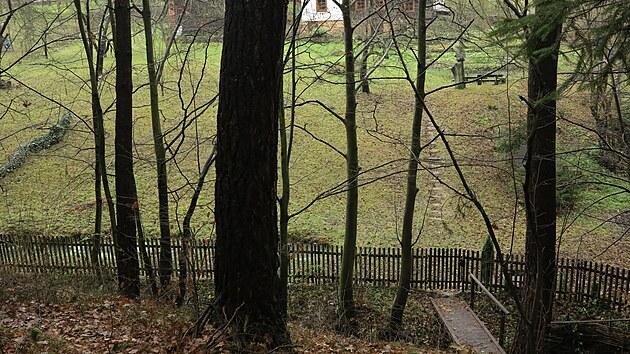 Pohled na zahradu s dřevěnkou a stodolou z lesa na protějším kopci.