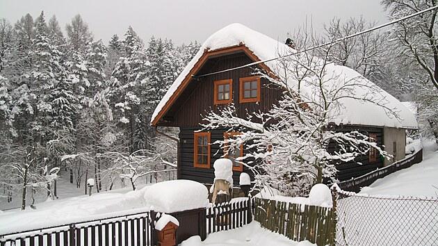 Zahrada u dřevěnky pod příkrovem sněhu.