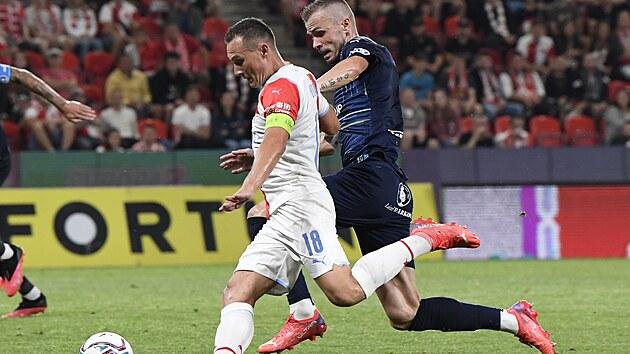 Slávistickı obránce Jan Bořil přihrává na gól okolo Stanislava Hofmanna ze Slovácka.