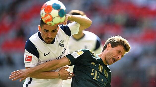 Danilo Soares z Bochumi v souboji s Thomasem Müllerem z Bayernu Mnichov