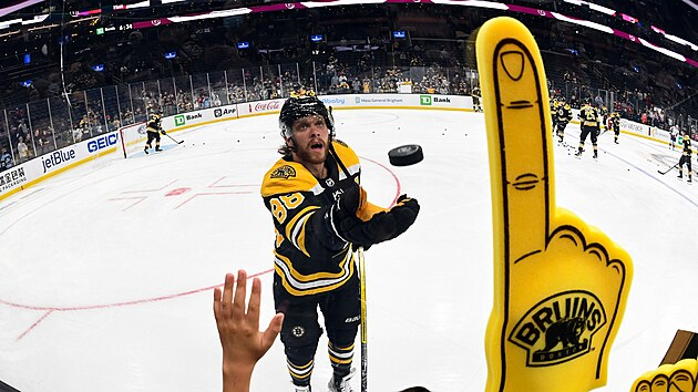 David Pastrňák hází puk fanouškům Bostonu.