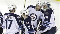 Winnipeg Jets goalie Ondrej Pavelec (31), from the Czech Republic, celebrates with teammates after the Jets defeated the San Jose Sharks 5-4 in an NHL ...