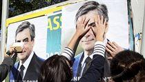 Voličky konzervativce Francoise Fillona vylepují na ulici jeho plakáty.