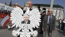Muž drží polskou orlici s fotkou zemřelého prezidenta Lecha Kaczyńského.