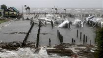 Storm Surge retreats from inland areas, foreground, where boats lay sunk and...