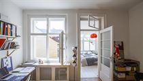 Pohled do ložnice, kterou odděluje okno a prosklené dvěře