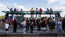 Část lidí sledovala demonstraci ze střechy tramvajové zastávky.