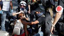 Protestující ošetřují zraněnou ženu