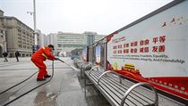 Pracovník čistí lavičky před budovou hlavního nádraží v čínském Wu-Chanu, v 11...