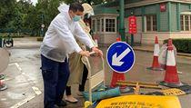 Zaměstnanci Disneylandu v Hong Kongu instalují ceduli s oznámením o přerušení...