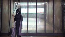 Cestující s obličejovou maskou prochází plastovımi děliči na stanici metra v...