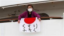 Žena drží japonskou vlajku s nápisem nedostek léků.