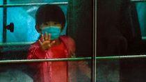 Dítě mává z vozidla, zatímco je odváženo z budovy v Hongkongu, kde se potvrdila...