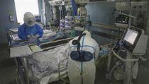 Zdravotníci kontrolují stav pacienta nakaženého koronavirem.