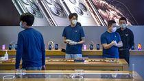 Zaměstnanci prodejny Apple Store v Číně chránící se před nákazou novım...
