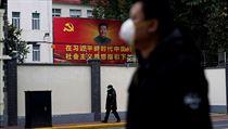 Lidé s rouškami procházejí v Šanghaji kolem portrétu čínského prezidenta Si...