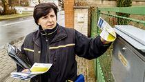 Poštovní doručovatelka roznáší informační letáky o koronaviru.