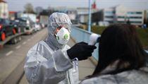 Polskı pracovník měří teplotu na německé hranici.