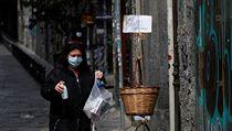 Žena v Neapoli daruje věci do košíku pro potřebné.