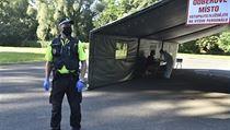 Policista stojí před odběrovım místem v areálu nemocnice v Karviné-Ráji, kde se...