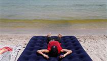 Muž odpočívá na pláží v Palermu.